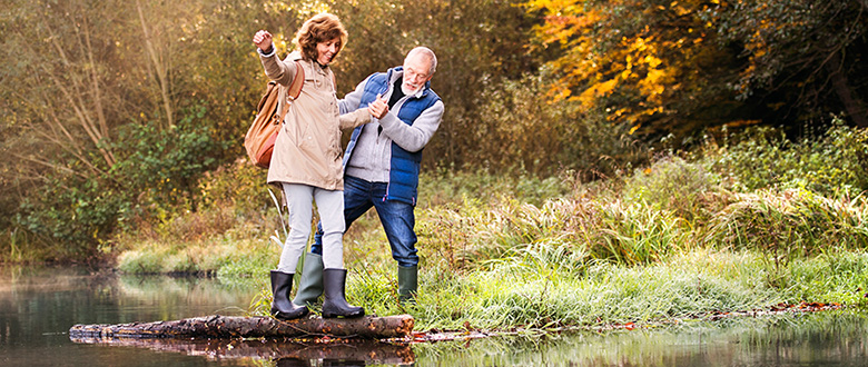 Balance Exercises to Prevent Falls. Active senior couple on a walk in a beautiful autumn nature. A woman and man by the lake in the early morning.